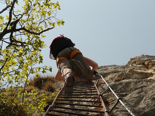 homem subindo escada na montanha em escalada