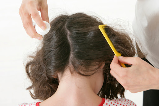 mulher penteando o cabelo de menina piolhenta
