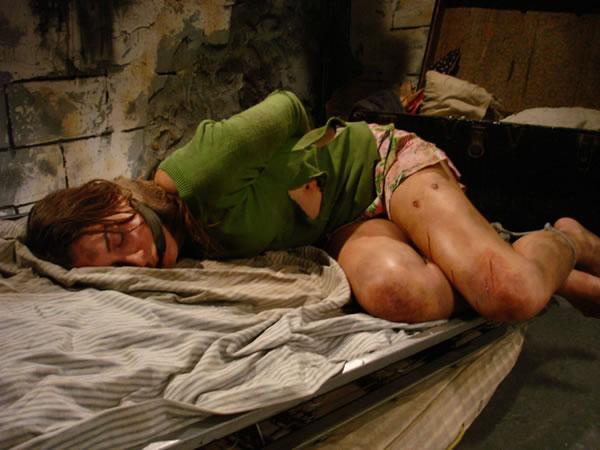 mulher amarrada deitada na cama e sendo torturada por sequestradores em uma cena do filme a garota da casa ao lado