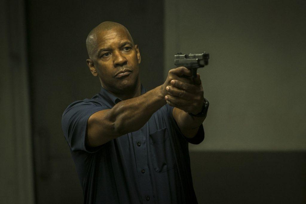 O protetor com uma arma na mão no filme