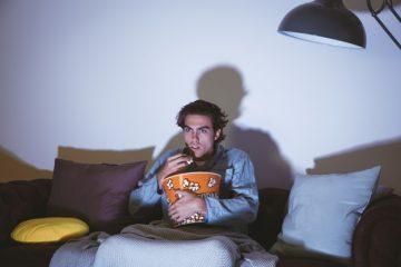 homem assistindo filme de terror sozinho na sala comendo pipoca