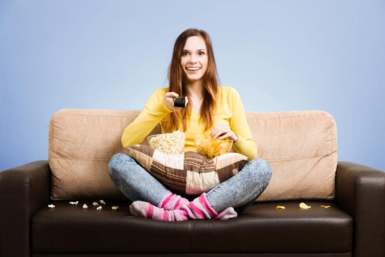 mulher sentada no sofá feliz comendo pipoca com o controle da televisão na mão