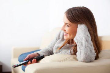 mulher deitada no sofá sorrindo assistindo um filme de comédia brasileiro
