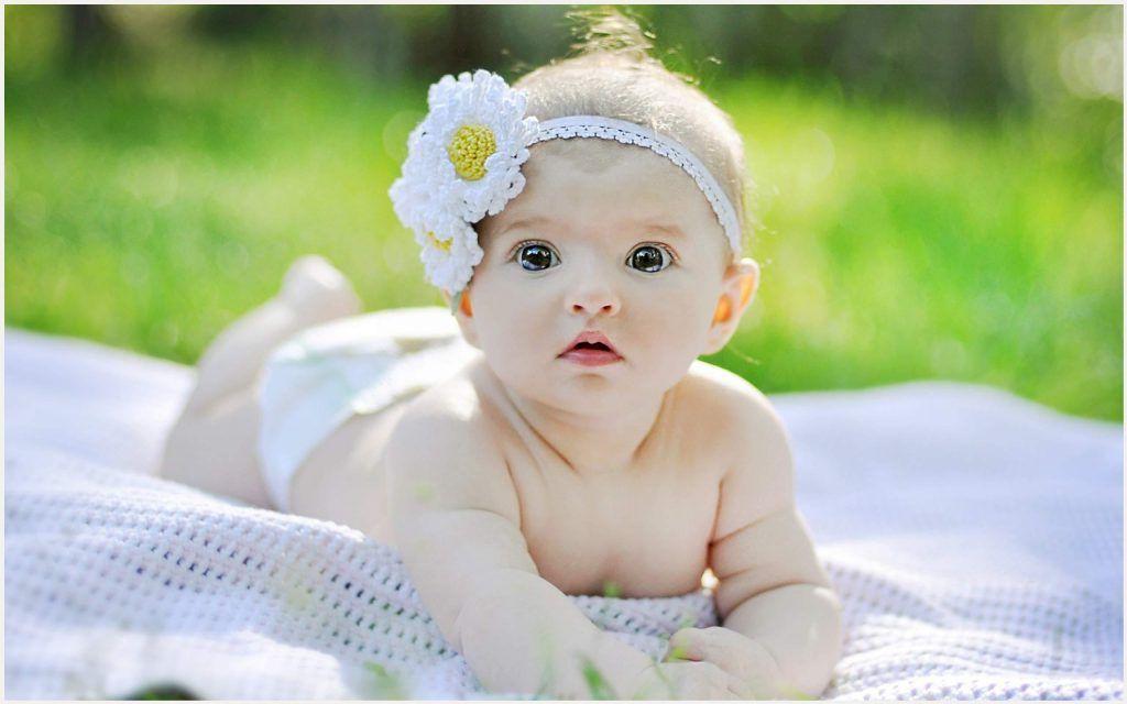 menina bebe pequena com uma flor na cabeça