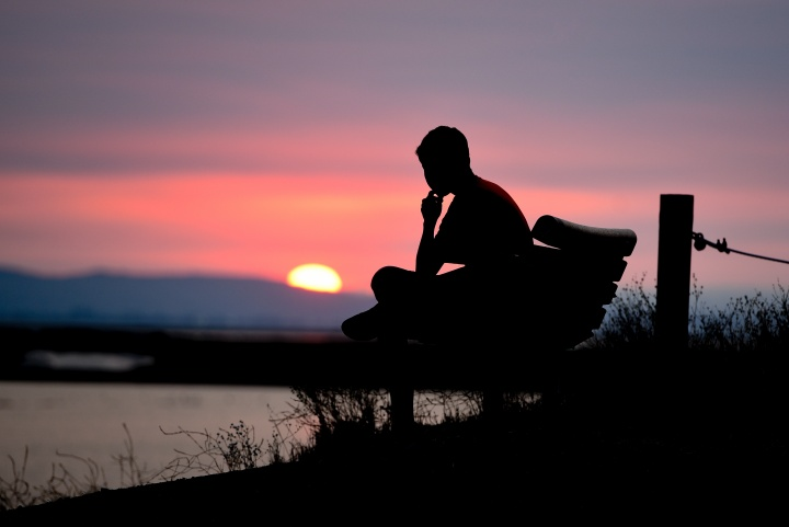 homem sentado apreciando a paisagem pela manhã