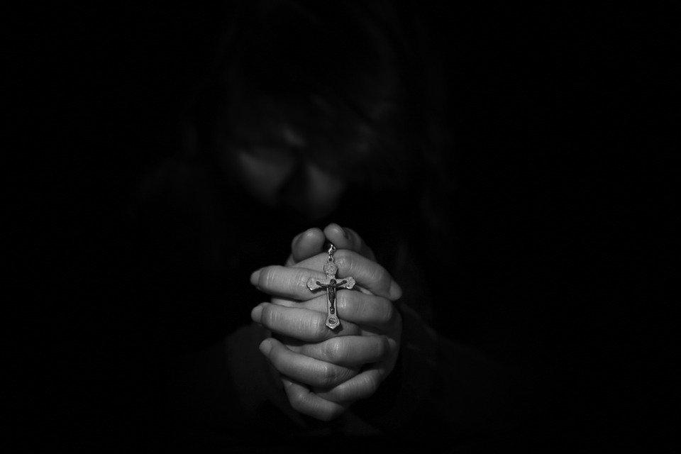 mãos juntas que oram e pedem perdão a Deus