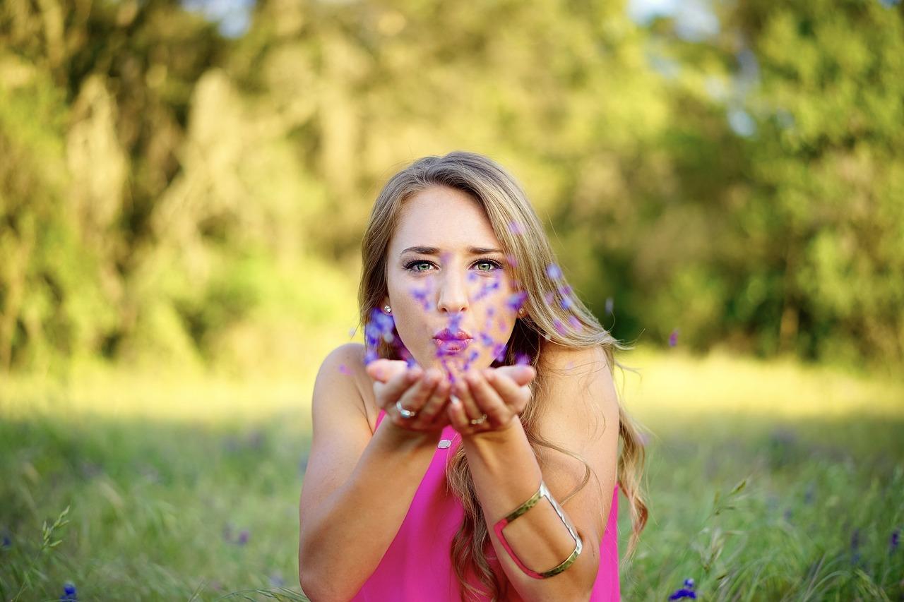 menina soprando flores ao ar livre