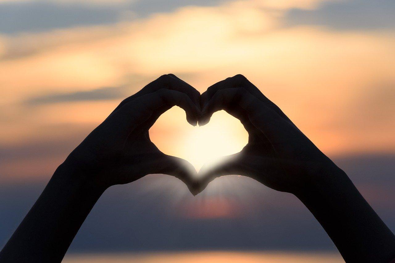 coração com as mãos ao nascer do sol