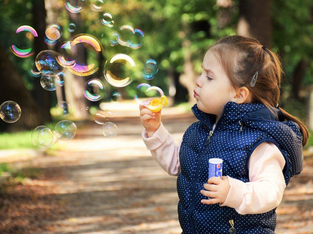 criança menina fazendo bolhas de sabão