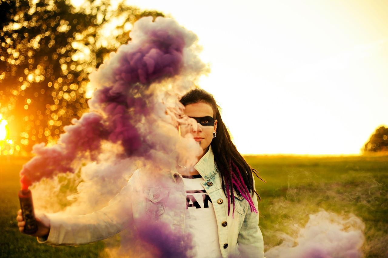 mulher fazendo fumaça com uma máscara no rosto