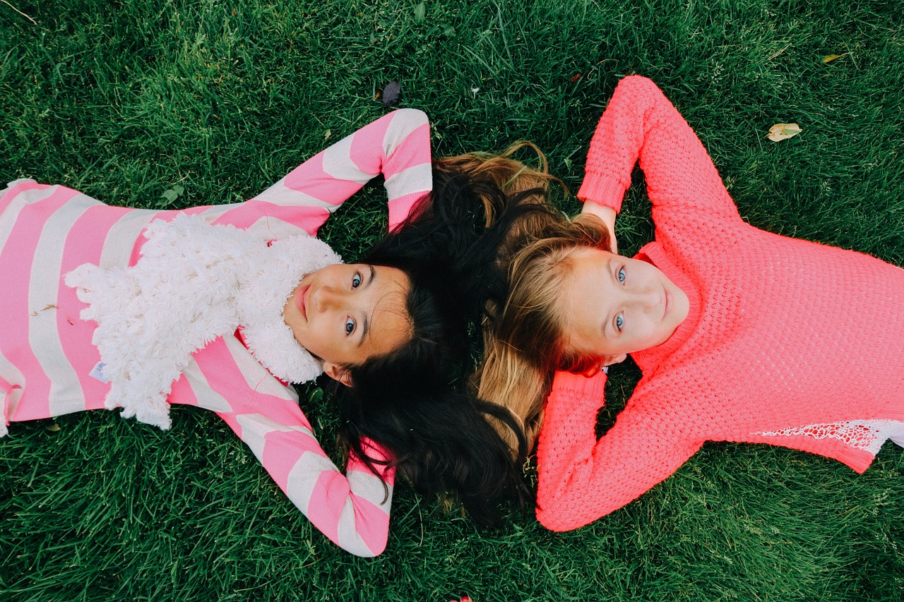 amigas de infância deitadas na grama brincando