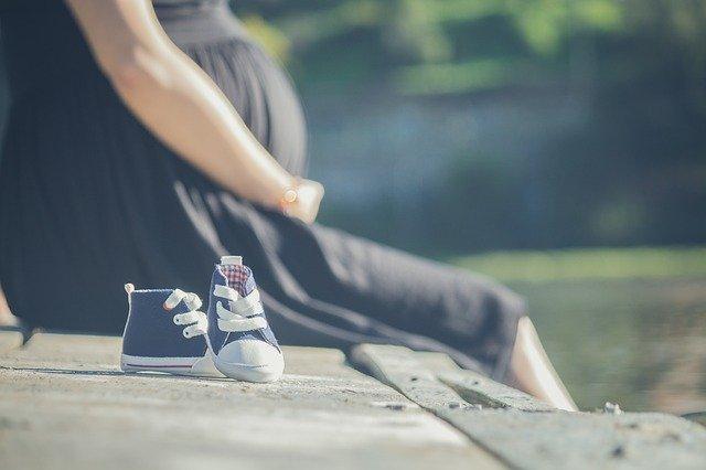 mulher grávida sentada e sapatinhos de bebê