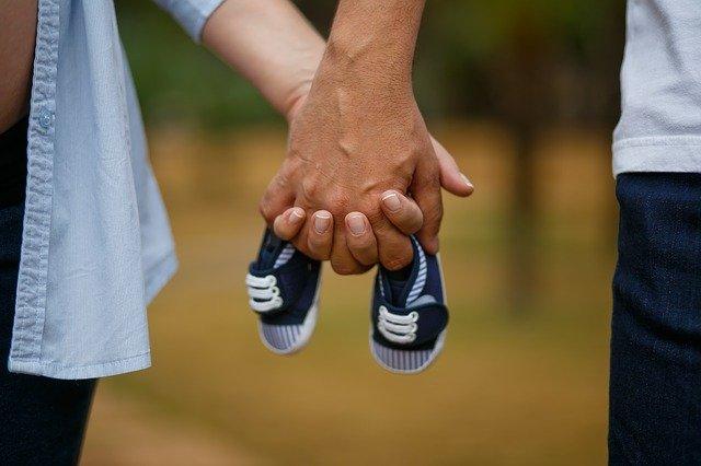 casal segurando os sapatos de um bebê