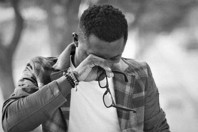 homem com a mão no olho segurando um óculos enquanto chora