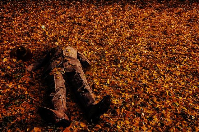 homem morto caído no chão em meio as folhas